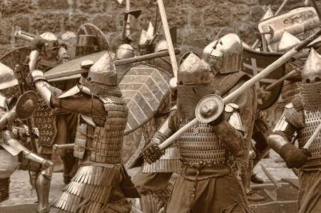 ch�teau m�di�val: Lutte entre les chevaliers pour pi�tons dans une armure lourde dans un ch�teau m�di�val contre un mur de pierre, Vyborg, en Russie, juillet-31
