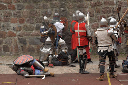 showmanship: Fight between the pedestrian knights in a heavy armor in a medieval castle against a stone wall ,  Vyborg,Russia, july-31