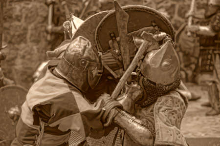 Fight between the pedestrian knights in a heavy armor in a medieval castle against a stone wall   Vyborg,Russia, july-31