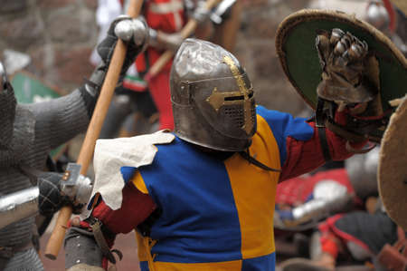 real renaissance: Fight between the pedestrian knights in a heavy armor in a medieval castle against a stone wall   Vyborg,Russia, july-31
