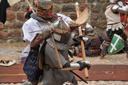 inquisition: Fight between the pedestrian knights in a heavy armor in a medieval castle against a stone wall  Vyborg,Russia, july-31