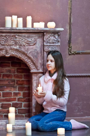 The girl the teenager at a fireplace with candles Stock Photo - 12414313