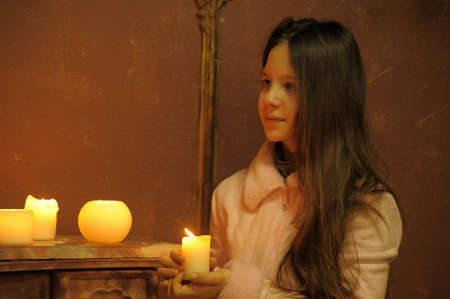 The girl the teenager at a fireplace with candles photo