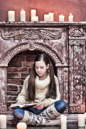 The girl the teenager at a fireplace with candles Stock Photo - 12414311