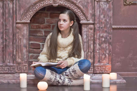 The girl the teenager at a fireplace with candles Stock Photo - 12414310