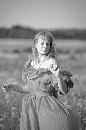 young woman in an old dress in the middle of the field photo