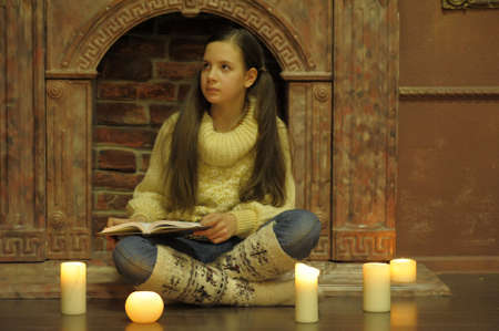 The girl the teenager at a fireplace with candles Stock Photo - 12442998