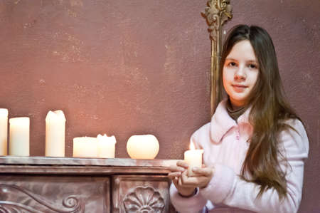 The girl the teenager at a fireplace with candles Stock Photo - 12443000