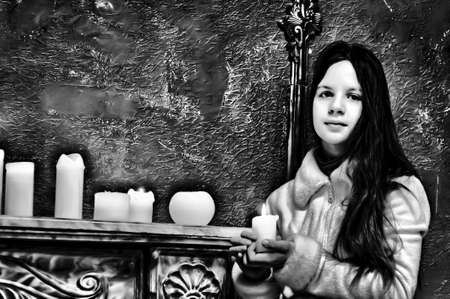 The girl the teenager at a fireplace with candles Stock Photo - 12442981