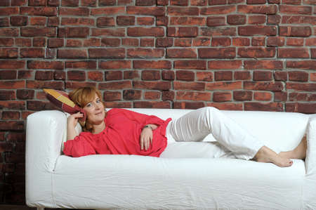 30 years old: woman lying on the sofa relaxing Stock Photo
