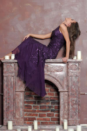 the girl sitting on a fireplace Stock Photo - 13280703