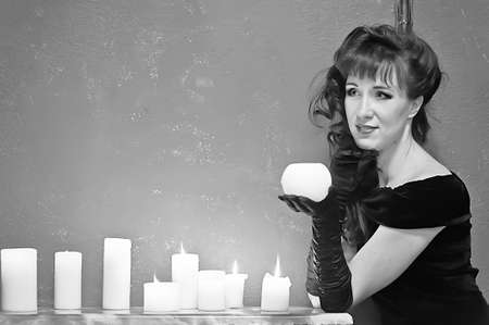 the young beautiful woman in a black dress from candles in a hand photo