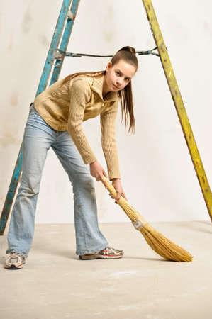 work task: teen girl with a broom sweeping the floor