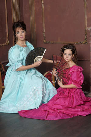 Two ladies in medieval dresses photo