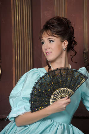 dressups: The young woman in an ancient blue dress with a fan in hands