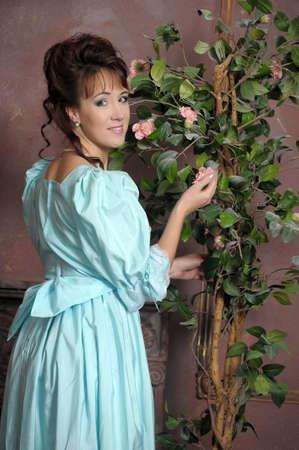 vestidos de epoca: La joven mujer en un vestido azul antiguo con un abanico en las manos Foto de archivo