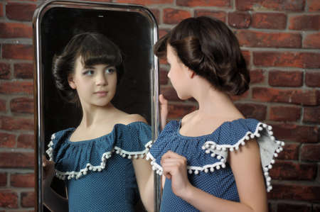 admires: the girl admires itself in a mirror Stock Photo