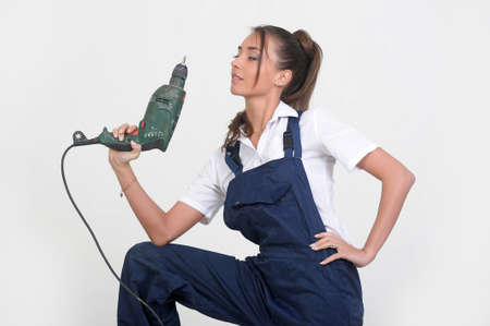 Closeup of a beauty girl with drill machine on white background photo