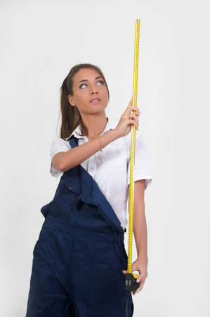 Young woman in overalls with a measuring tape  photo