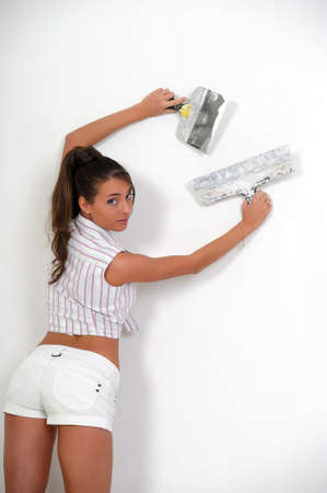 messy room: Girl plastering the wall  Stock Photo