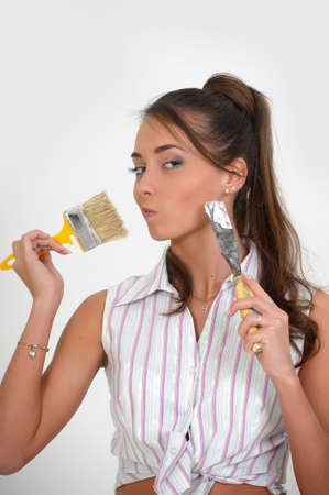 Image of a beautiful girl on white, holding paint brush photo