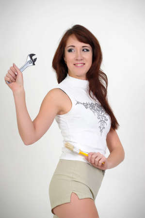 Beautiful young do-it-yourselfer holding a screw-wrench Stock Photo - 12598772