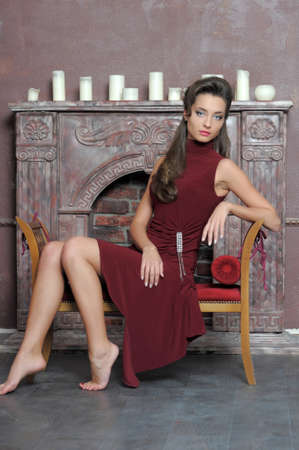 Brunette is resting on the couch by the fireplace Stock Photo - 14408495