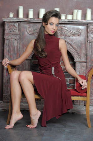 Brunette is resting on the couch by the fireplace Stock Photo - 14412093