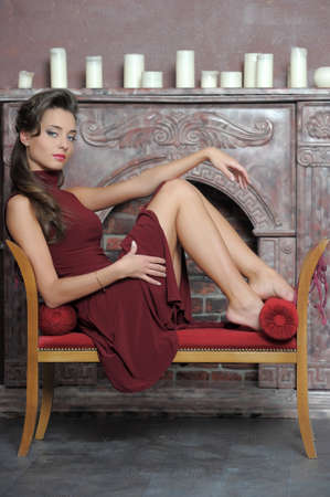 Brunette is resting on the couch by the fireplace Stock Photo - 14408488