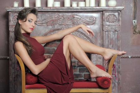 Brunette is resting on the couch by the fireplace Stock Photo - 14408795
