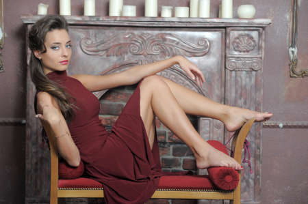 Brunette is resting on the couch by the fireplace Stock Photo - 14412056