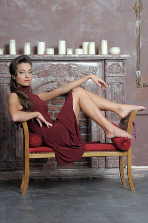 Brunette is resting on the couch by the fireplace Stock Photo - 14412091