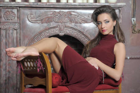 Brunette is resting on the couch by the fireplace photo