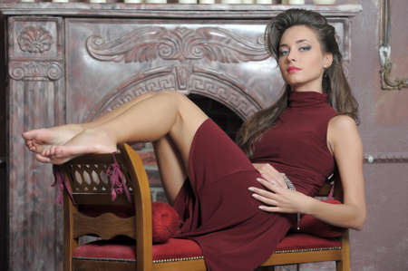 Brunette is resting on the couch by the fireplace Stock Photo - 14412057