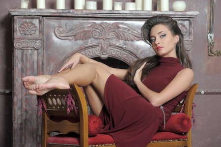 Brunette is resting on the couch by the fireplace Stock Photo - 14410181