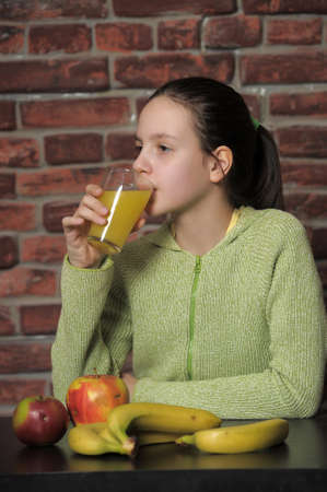 Girl with fruits and glass of orange juice photo