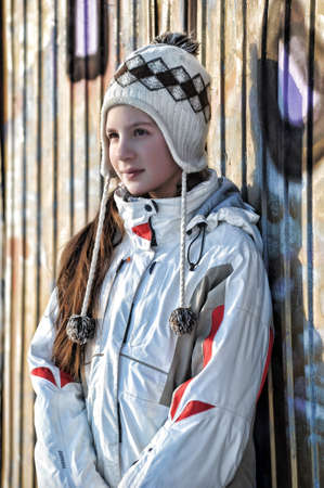 Teen girl in a sports jacket and hat against the wall with graffiti Stock Photo - 17061265