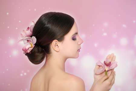 The beautiful girl with orchids in a hairdress and in hands photo