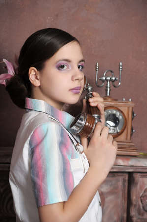 Girl calling on a old telephone Stock Photo - 13570652