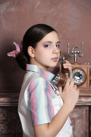 Girl calling on a old telephone photo