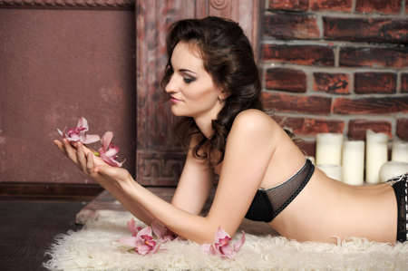 young woman in a bra with orchids photo