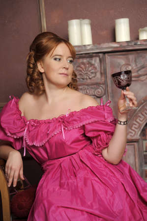 portrait of the woman in a medieval dress with a glass in hands photo