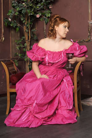 tree dweller: the lady of the Victorian era in a crimson dress in an interior