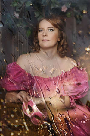 portrait of the woman in a medieval dress behind glass with rain drops photo