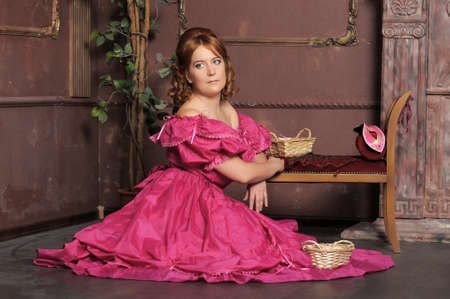 the lady of the Victorian era in a crimson dress in an interior photo