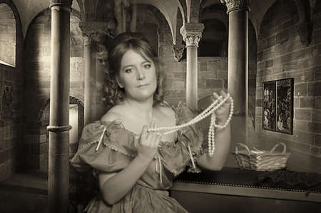 the medieval lady with a pearl necklace in hands photo