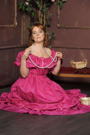 la dama medieval con un collar de perlas en las manos photo