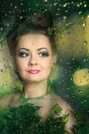 The girl behind wet glass from a rain Stock Photo - 13152796
