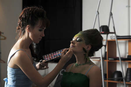 Model getting some vivid make-up applied before a fashion photoshoot  Stock Photo - 13147057
