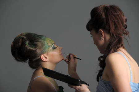 Model getting some vivid make-up applied before a fashion photoshoot Stock Photo - 13147048